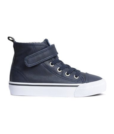 High tops in imitation leather with elasticized laces, Velcro tab at top, and patterned fabric lining. Rubber soles.