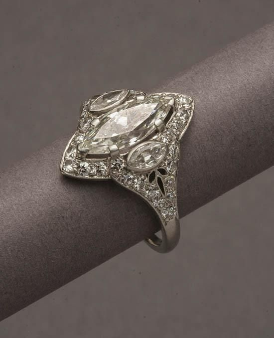 <b>Edwardian Platinum Solitaire Diamond Ring</b> <br /> <i>Circa 1910</i> <br /> The marquise-shaped mount centered with one marquise-cut diamond weighing approximately 1.20 carats, flanked by two marquise-cut diamonds weighing approximately .20 carats and surrounded by thirty-two round full-cut diamonds weighing approximately .50 carats. <br /> <i>Total weight of diamonds: 1.90 carats <br /> Gross weight: 2.6 dwt. <br /> Length of ring: 5/8 in (1.58 cm) <br /> Shank size: 6-1/2</i>Property…