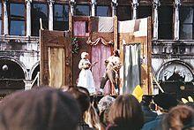 COMEDIA del ARTE  Tablado con una representación callejera de la Commedia dell'Arte, en la Plaza de San Marcos durante el Carnaval veneciano de 1999. La comedia del arte (Commedia dell'Arte) o comedia del arte italiana es un tipo de teatro popular nacido a mediados del siglo XVI en Italia y conservado hasta comienzos del siglo XIX. Como género, mezcla elementos del teatro literario del Renacimiento italiano con tradiciones carnavalescas (máscaras y vestuario), recursos mímicos y pequeñas…