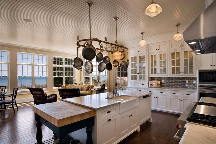 coastal kitchen with farmhouse sink in island and windows looking at ocean