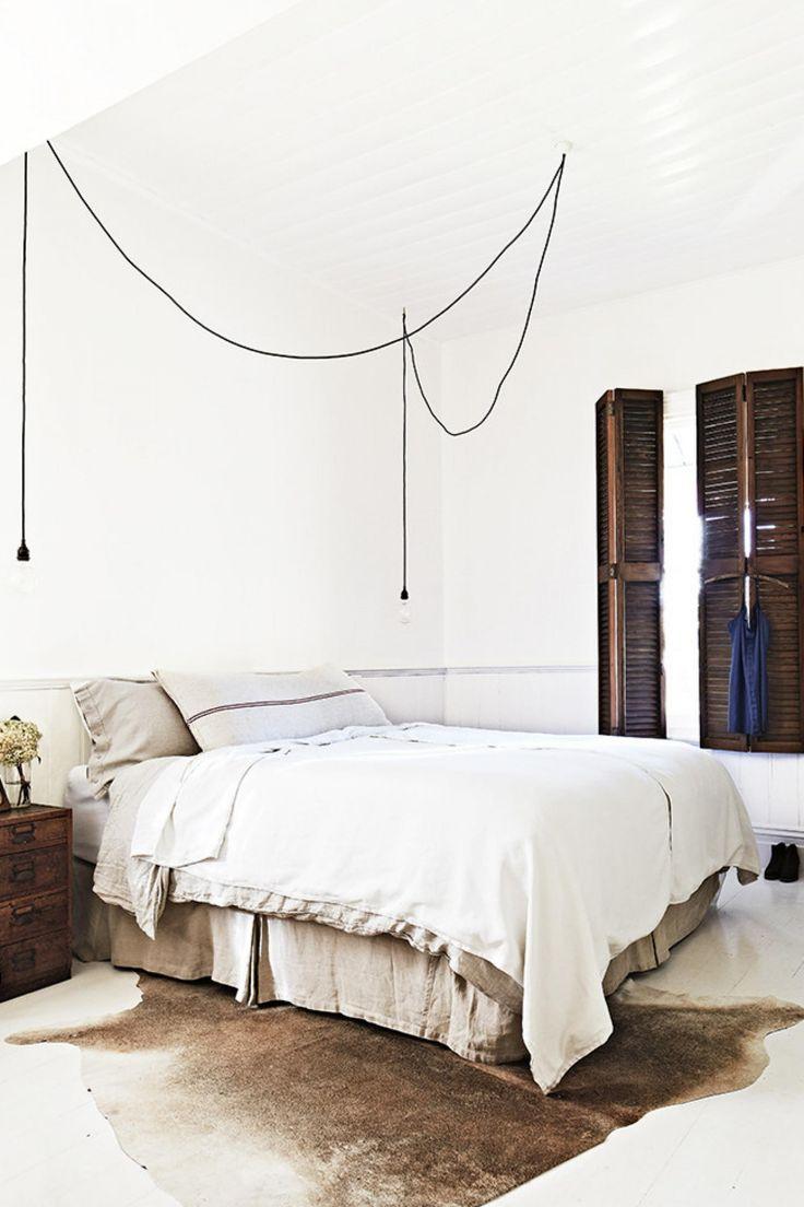 white rustic bedroom linen industrial wood doors exposed bulbs