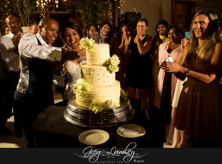 Cake Cutting with flowers.  Three tiered wedding cake.