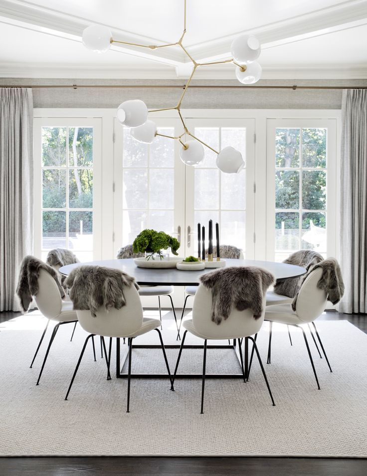 Stunning scandinavian dining room with large round table white chairs faux fur hung over the chairs white french doors and abstract lighting tamara