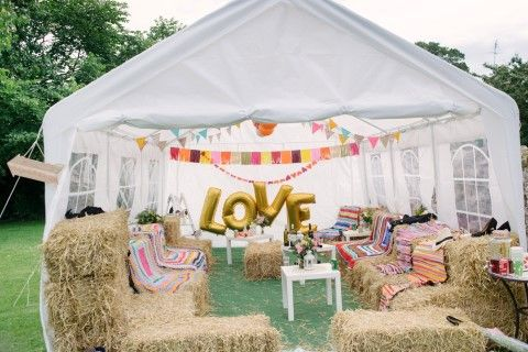 Outdoor wedding reception with a tent, hay bales and bunting at Tyninghame Village Hall