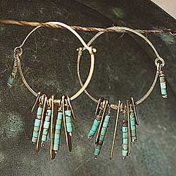 """Delicate, hand-hewn """"feathers"""" made of high-copper brass form earrings that are at once subtle and striking. Earthy with just the right amount of sophistication, these earrings feature eye-catching and tiny stacked turquoise beads dangling from pivoted brass hoops."""