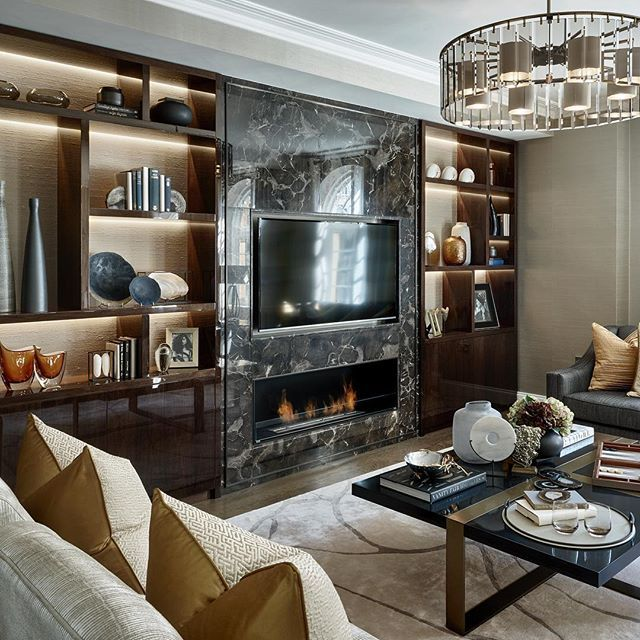 The living room at our recently completed apartment on Sloane Street with marble and walnut joinery wall, backlit with textured wallpaper and bronze inlay detail #interiorarchitecture #interiordesign #interiorstyling #luxuryinteriors #laurahammett