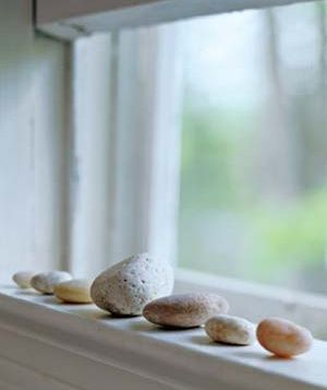 A row of smooth stones on a shelf or a windowsill is a pleasant reminder of beach walks and creates a spot of Zenlike calm in a room.