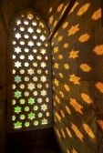 arabic window : Qutb Minar, Delhi, carvings in the sandstone of a window gives a pattern of sky with stars Stock Photo