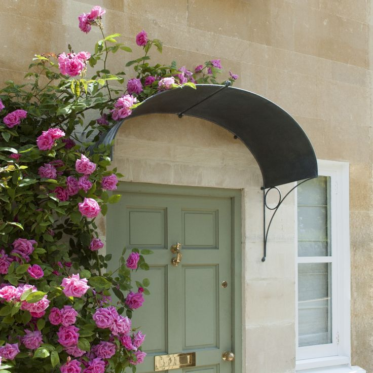 Climbing pink roses over a gentle ellipse front door canopy. Designed and made from quality steel in England. www.garden-requisites.co.uk