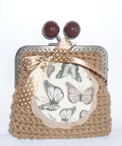 Carteira feita em linha barbante na cor castanho claro. Fecha com fecho metálico e a decorar tem uma aplicação em feltro com borboletas e um laço dourado. Tamanho aproximado: 11cm x 11cm Preço: 5€