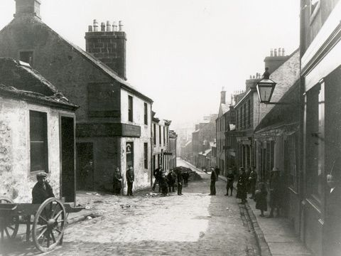 Black and white view down New Street, Paisley. The cobbled street is lined by one and two-storey buildings. A number of people in Edwardian dress, including a man resting against a two-wheeled cart, look towards camera.