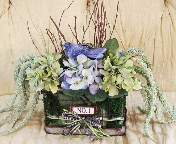 Floral arrangement with blue bird nest blue and green theme