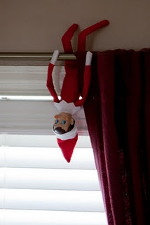 Elf on the Shelf hanging upside down on the curtain rod.