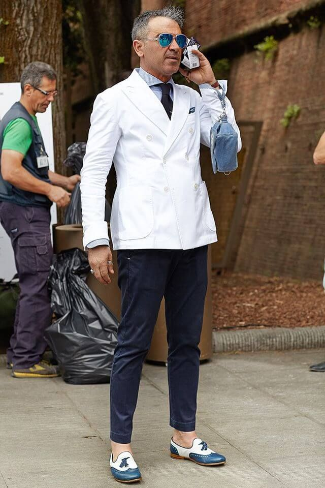 白ダブルジャケットに紺のパンツを合わせた着こなし