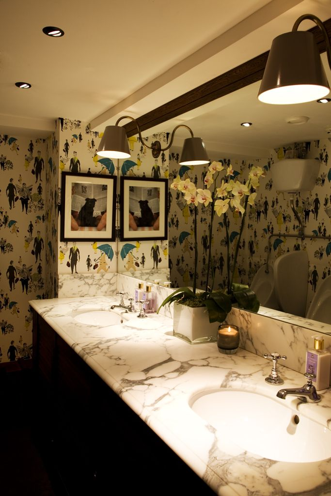 Beauchamp Club gents WC with Lizzie Allen wallpaper and mirror with lamps through. A project from 2010