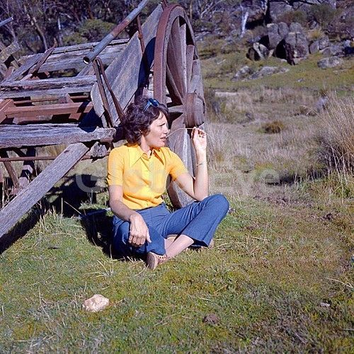 Woman in yellow blouse and blue jeans chewing straw seated on ground by old farm cart. Woman in yellow blouse and blue jeans chewing straw seated on ground by old farm cart. Photograph By David   Bigwood #PeoplePhotography