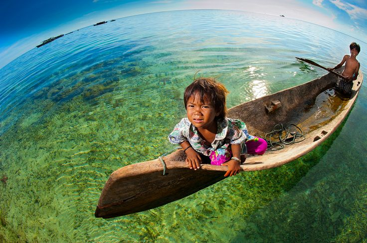 An outstanding fisheye image of a Malaysian girl boating through gorgeous and pristine waters. Image by Mata Arif.
