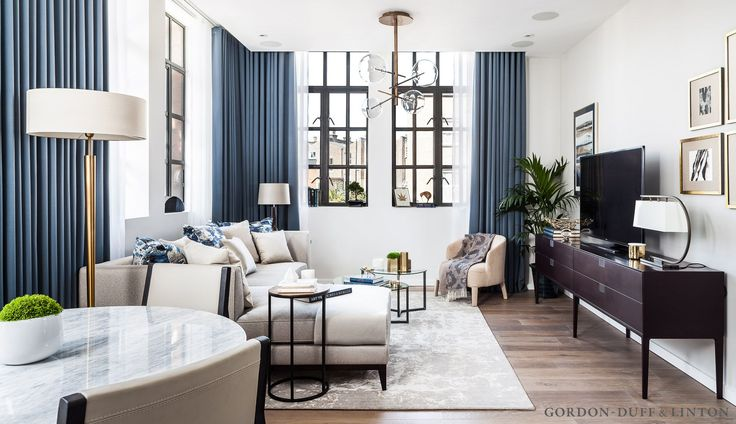 Living room with ornate chandelier, L-shaped sofa, recessed curtain tracks and brass details. Old factory conversion in North London with crittall windows. Saarinen marble dining table and two-tone leather and dark wood chairs.
