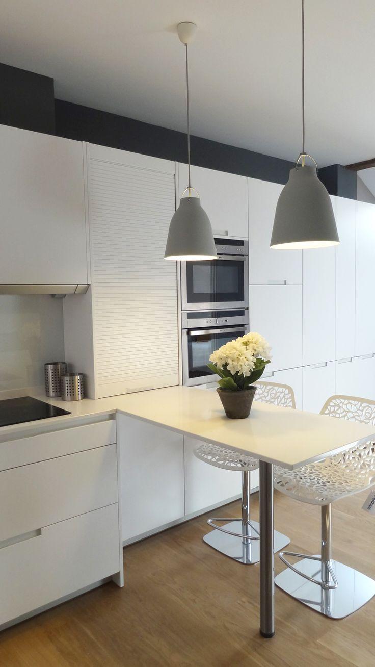 Una cocina compuesta por frentes en L con una cómoda barra para desayunos y comidas informales. Los suelos aportan calidez y las franjas elegancia y amplitud al modelo más versátil de Santos. Los hornos compactos son de Neff