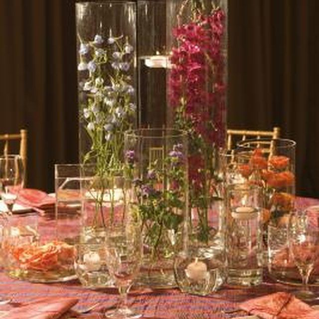 A submerged centerpiece is arranged in glass vases and cylinders.