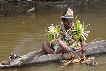 Fishing along the Sepik River is traditionally the domain of women. She lights a small fire on her dug-out canoe to ward-off mosquitoes and also cure the fish.