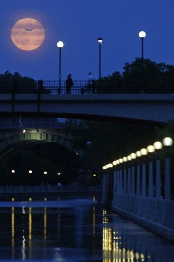 Aircraft passes in front of a Supermoon rising over the Rideau Canal in Ottawa July 12, 2014. Occurring when a full moon or new moon coincid...