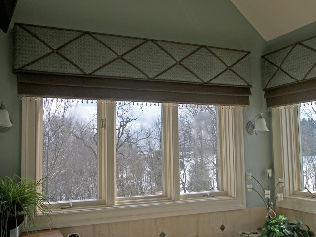 """X-Traordinary Cornice Board- This cornice is tufted, """"x-ed"""" with ribbon, and studded in the center of each cross intersection. A mock Roman shade hangs beneath that is edged with a beaded trim."""