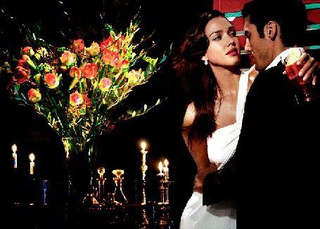 Влюбленная пара обнимаются, на фоне букета роз, горящих свечей и флаконов с парфюмерией