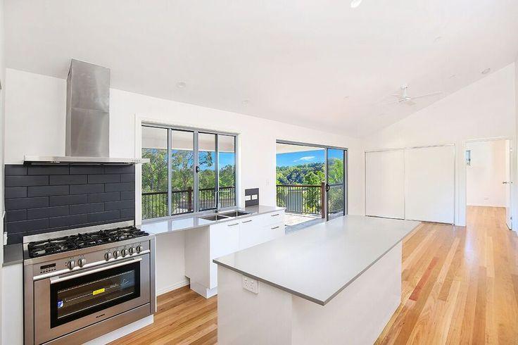 Open plan living kitchen area with real timber flooring & TechniStone concrete look benchtops   Tru-Built Builders Queensland