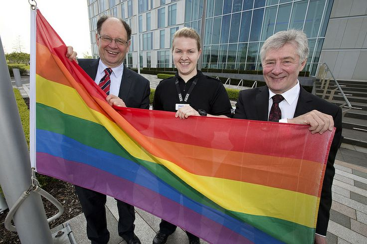 Police and Crime Commissioner Tony Lloyd and his deputy Jim Battle hoist the flag with PC Claire Campbell of GMP's Pride network.  Greater Manchester Police is flying the rainbow flag at its headquarters and other police stations tomorrow to mark International Day Against Homophobia, Biphobia and Transphobia.