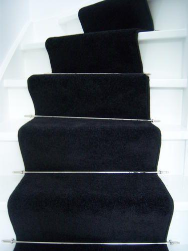 Zwarte traploper op witte trap