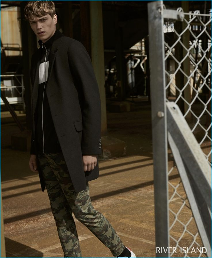 English model Jake Love layers River Island's black zip color block jacket with a black smart overcoat.
