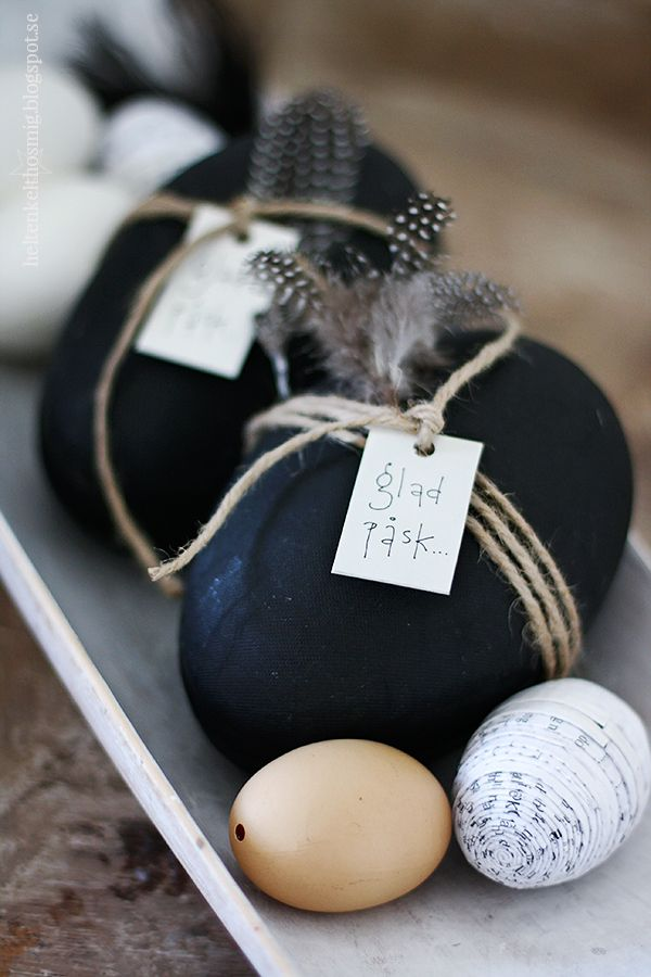 black Easter eggs tied up with string and feathers