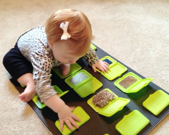 Peek a Boo Sensory board using wipes lids