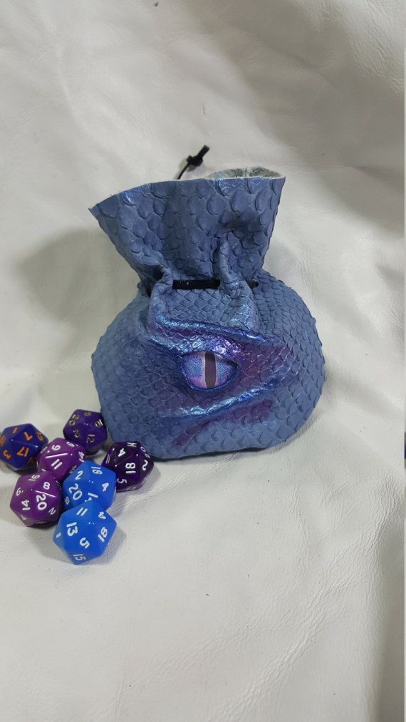 A Beautiful Blue Dragon Scale Leather Dice Bag With A Blue/Purple Dragons Eye.  The Leather is Embossed and Looks like real Dragon Scales.  Small size.. 5 Tall by 5 Wide..... Holds Up to 21 Dice .  It Has Blue/Purple Shimmer Highlighting around the Eye.  Closes With Leather Thong and Spring Toggle.