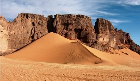 Landscape of bizarrely shaped desert mountains and innumerable rock carvings