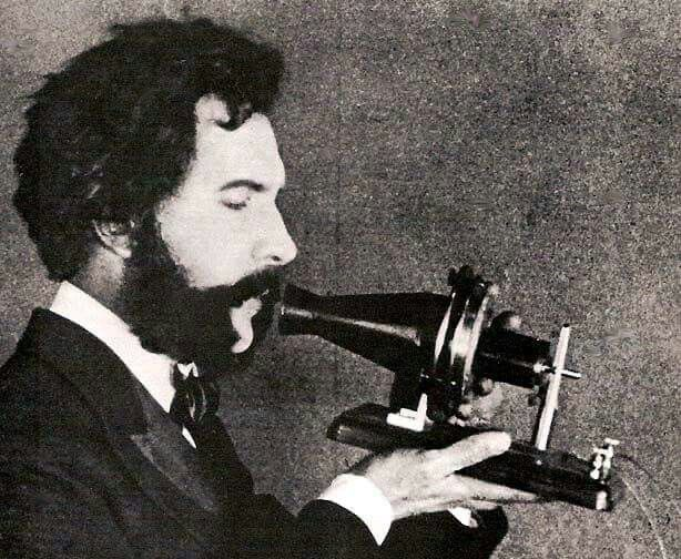 Alexander Graham Bell speaking into a telephone in 1876.