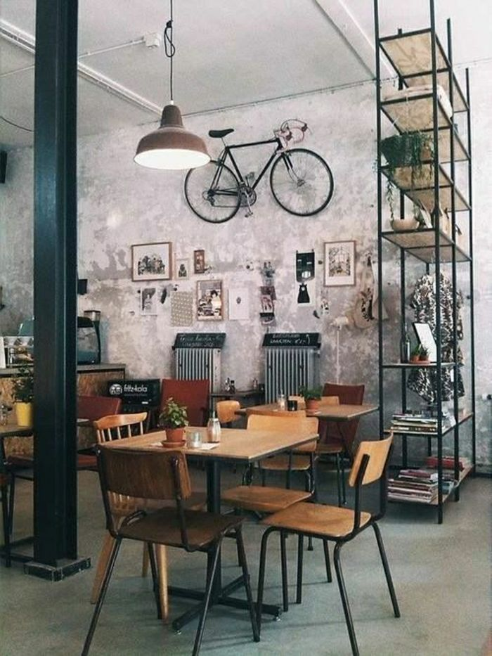 wide atypical loft with a decorative bicycle was put on the wall, hanging chandelier, gray wall