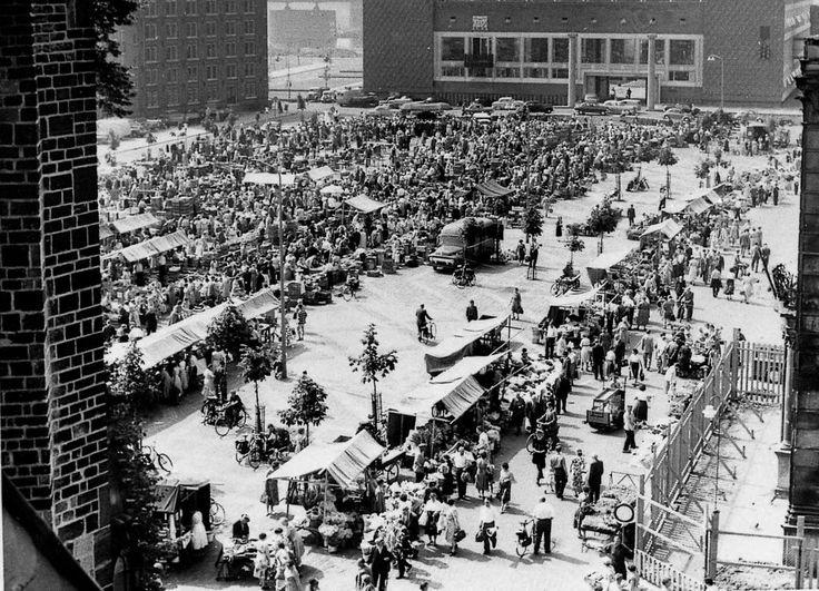 Marktdag op de Markt in 1960. Rechts onderaan zien we hekken rond de Waag staan. Dat monumentale pand, zwaar beschadigd in de oorlog, werd middels een restauratie van 1959 tot 1961 weer volledig in oude luister hersteld. Links bovenaan het oude Rijksarchief, afgebroken in 1968. Rechts bovenaan het Provinciehuis, in 1954 in gebruik genomen.