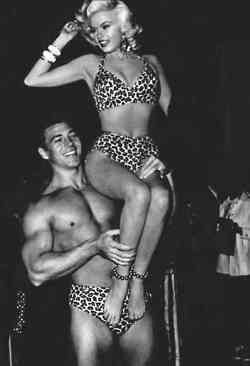 "Jayne Mansfield in Classic Bikini, lifted on high by her hubby Mickey ""Body Builder"" Hargitay..."