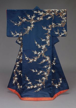 Furisode with shortened sleeves, Japanese, Edo period, mid-19th century, Silk satin embroidered with silk and gilt-metallic yarns. Dark blue silk satin ground with design of plum blossoms embroidered with white, brown and light green silk and gilt-metallic yarns. Lined with bright red silk and padded at the bottom. Red silk crepe sleeve facings. Style favored by wealthy merchant class (chônin). MFA