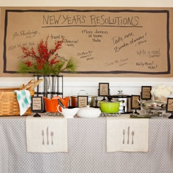 Summon the neighbors to a relaxed potluck dinner where everyone contributes. Graphic table linens provide cohesion to the mishmosh of pots you can expect. Have guests write dish names on brown kraft paper slipped into footed frames; a paper wall banner displays their resolutions. Add plenty of serving utensils, trivets, and a basket for bread.
