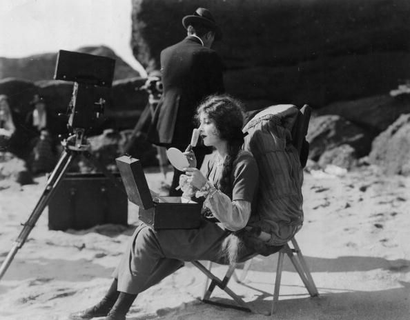 Mildred Harris the American leading lady and first wife of Charlie Chaplin is applying makeup on the beach between production shoots