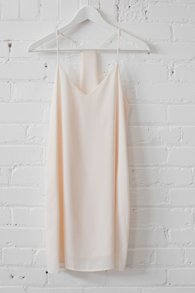 "Lovely neutral minimalist dress featuring fully lined soft sheer material. Racer-back and a V-neckline with thin spaghetti straps. Comfortable and casual loose fit. Size small measures approx. 33"" in length.   100% Polyester Made in USA"