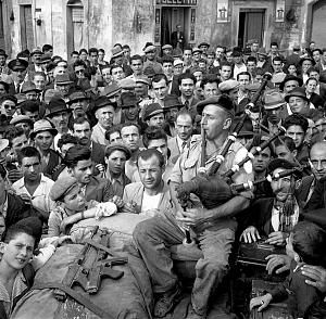 Caption: Piper Roderick Grant of the 48th Highlanders of Canada playing his bagpipes for a crowd of liberated civilians, Matera, Italy, 24 September 1943 Source: LAC - PA-209414