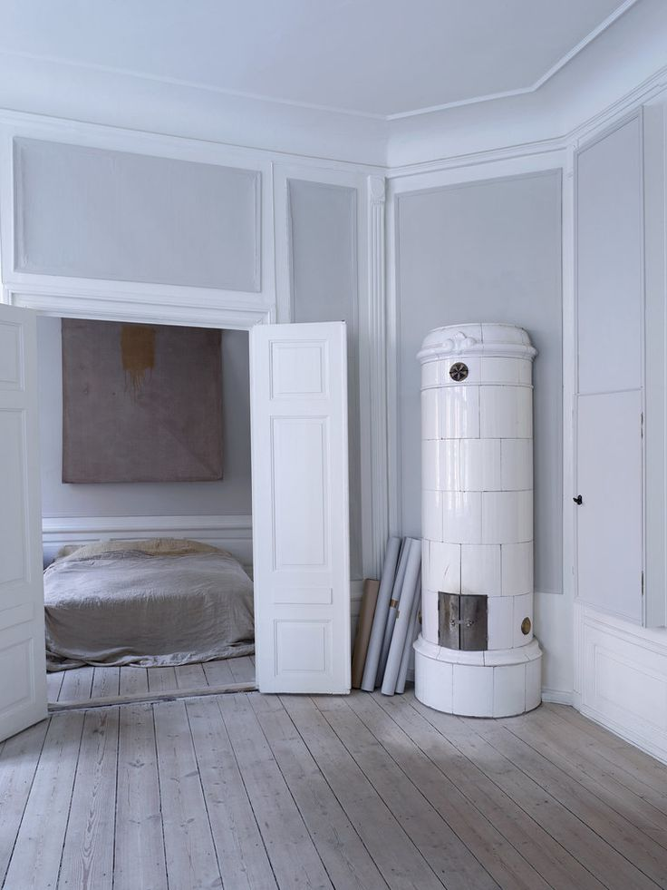 In Gustav's bedroom, a painting by Julia Haller hangs over a bed draped in vintage blankets of wool and hemp; the porcelain stove was added in the 19th century.