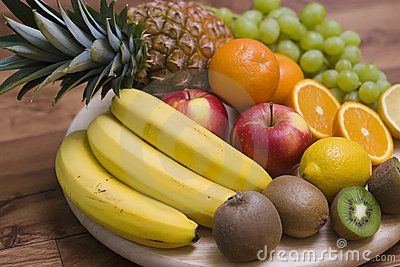 Colourful composition arranged on wooden chopping board, consisting of fresh fruit. The ingredients are: pineapple, bananas, kiwis, grapes, oranges.    <a href='http://www.dreamstime.com/food-photos-and-table-settings-rcollection4782-resi208938' STYLE='font-size:13px; text-decoration: blink; color:#FF0000'><b>MY FOOD PHOTOS »</b></a>