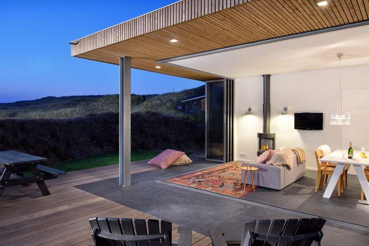 Binnen is buiten bij dit kleine vakantiehuisje op Vlieland. Doordat dat de aluminium deuren geheel geopend kunnen worden, het dak een luifel heeft en de tegelvloer van binnen naar buiten is doorloopt wordt het huisje optisch vergroot. Ontwerp BNLA architecten | Fotografie Sudio de Nooyer.