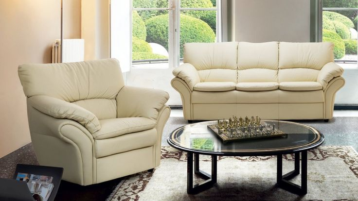 Zestaw wypoczynkowy w skład którego wchodzi mała 3-osobowa kanapa i wygodny fotel. Skórzany komplet wypoczynkowy w jasnym kolorze z wygodnym oparciem i szerokimi podłokietnikami.