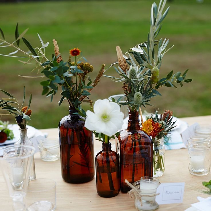 country fall party table  informal arrangement amber bottle poppies  eucalyptus  thistle